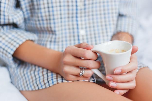 Frau im hemd sitzt auf bett mit einer schale mit heißem kaffee
