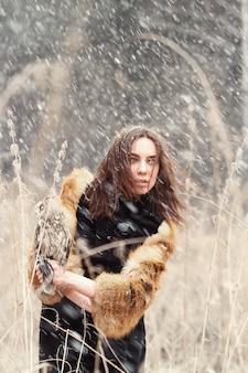 Frau im herbst im pelzmantel mit erstem schnee der eule an hand. schöne brunettefrau mit dem langen haar in der natur, eine eule halten. romantisch, zart aussehen frau