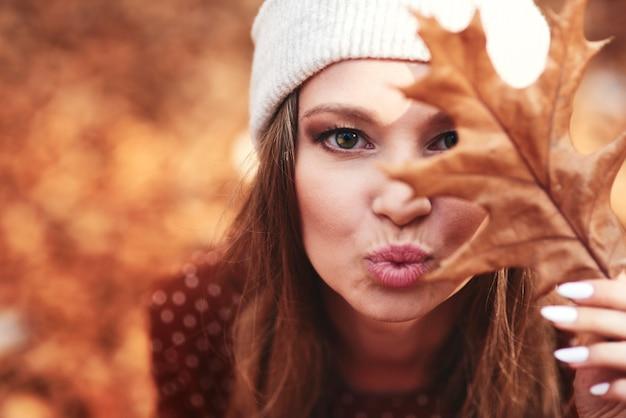 Frau im herbstlichen wald, die einen kuss fließt