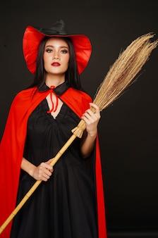 Frau im hexenhut und -kostüm mit besen im halloween-festival
