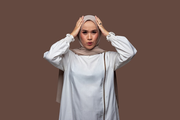 Frau im hijab, die kopf mit verwirrtem, schwindligem, besorgtem ausdruck hält