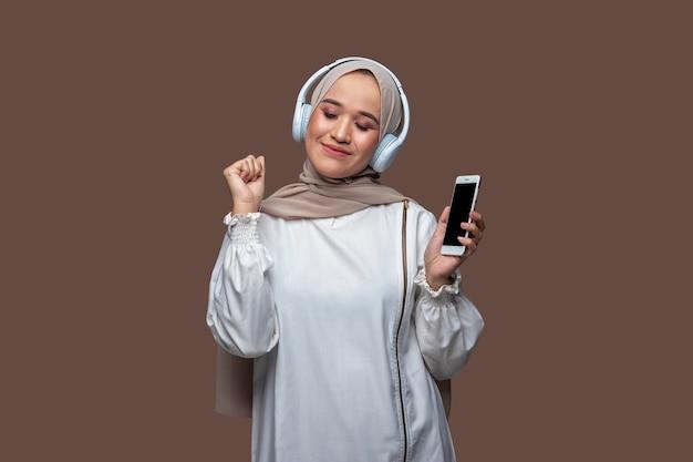 Frau im hijab, die musik von mobiltelefon und drahtlosen kopfhörern genießt