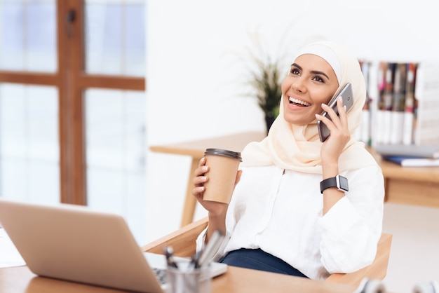 Frau im hijab hört musik über kopfhörer.