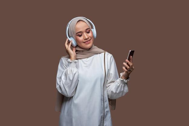Frau im hijab hört musik vom handy mit drahtlosen kopfhörern, während sie ihre augen schließt