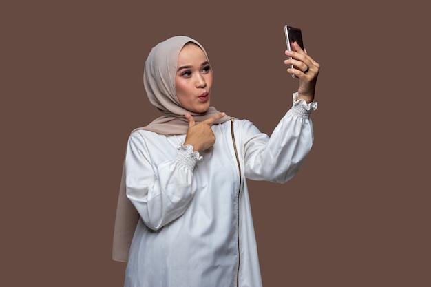 Frau im hijab macht ein selfie mit einem smartphone