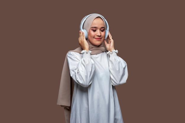 Frau im hijab posiert mit drahtlosen kopfhörern, während sie ihre augen schließt