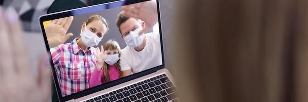 Frau im hintergrund winkt hand in laptop-bildschirm mit bild von mann, frau und kleinem mädchen