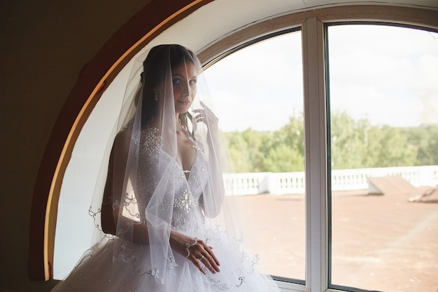 Frau im hochzeitskleid, das am fenster steht. braut, die auf hochzeitszeremonie wartet