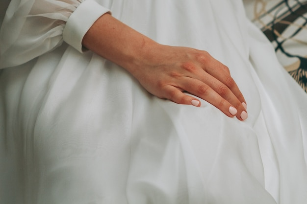 Frau im hochzeitskleid mit der hand am knie