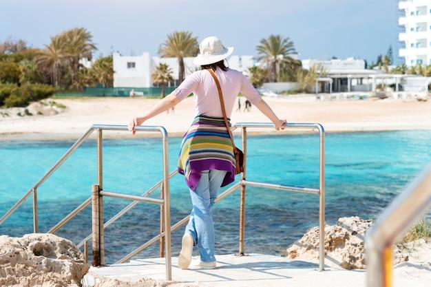 Frau im hut am strand. sommerferien, urlaub, reisen und personenkonzept