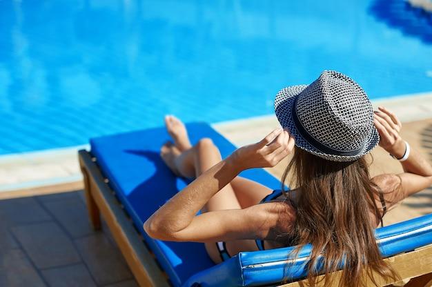 Frau im hut, der auf einem ruhesessel nahe dem swimmingpool am hotel liegt, nimmt ein sonnenbad