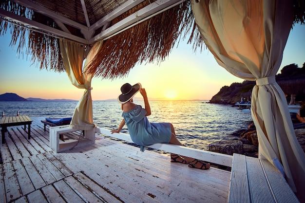 Frau im hut, der durch das meer in einem luxuriösen strandhotelresort bei sonnenuntergang entspannt, das perfekten strandurlauburlaub in bodrum, türkei genießt. outdoor seascape sommerreisekonzept