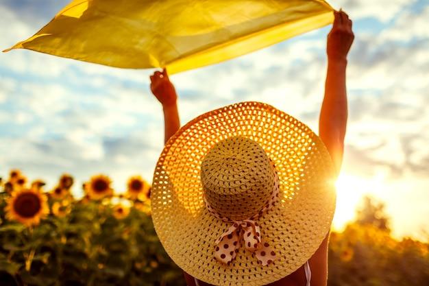 Frau im hut, der im blühenden sonnenblumenfeld entspannt, hob arme mit schal und hatte spaß. sommerurlaub