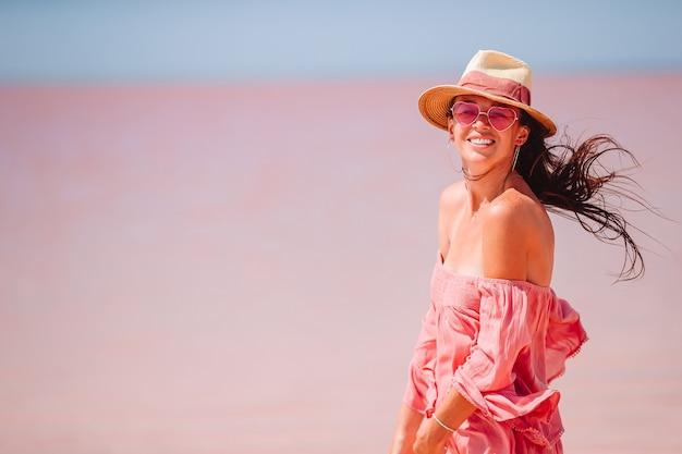 Frau im hut gehen auf einem rosa salzsee an einem sonnigen sommertag.