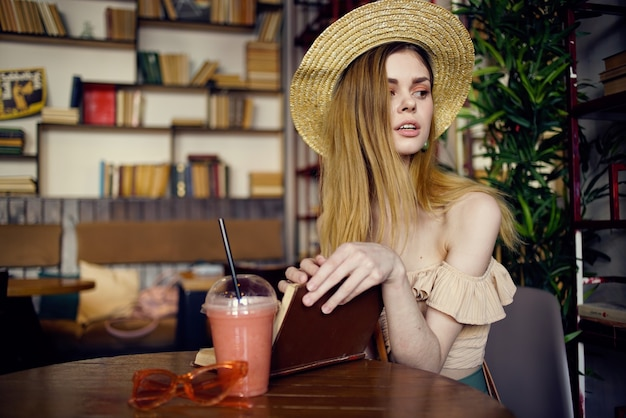 Frau im hut sitzt im kaffeekonto-trinkbuch-leseurlaub