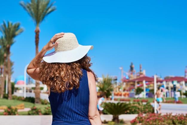 Frau im hut und im blauen kleid gehen im hotelerholungsort spazieren