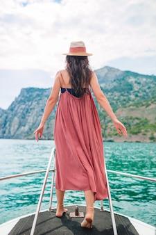 Frau im hut und im kleid, die auf boot im klaren offenen meer segeln