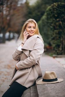 Frau im hut und im mantel im park am telefon sprechend