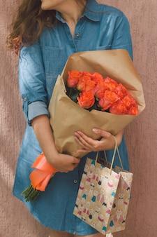 Frau im jeanskleid mit strauß rosen und geschenkpapierbeutel