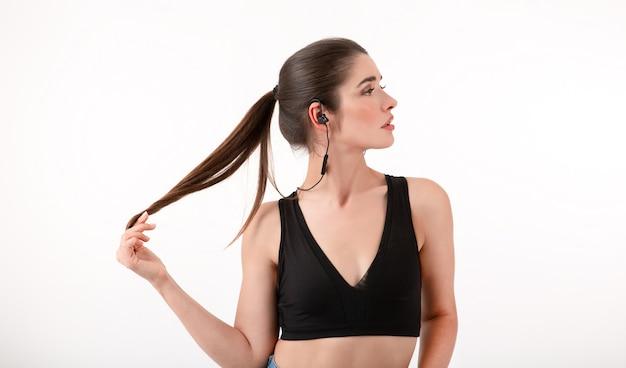 Frau im joggen schwarzes top musikhören über kopfhörer posiert isoliert auf weiß