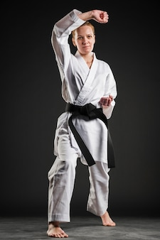 Frau im karate kimono posiert