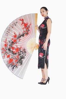 Frau im kimono, der mit großem seidenfan steht