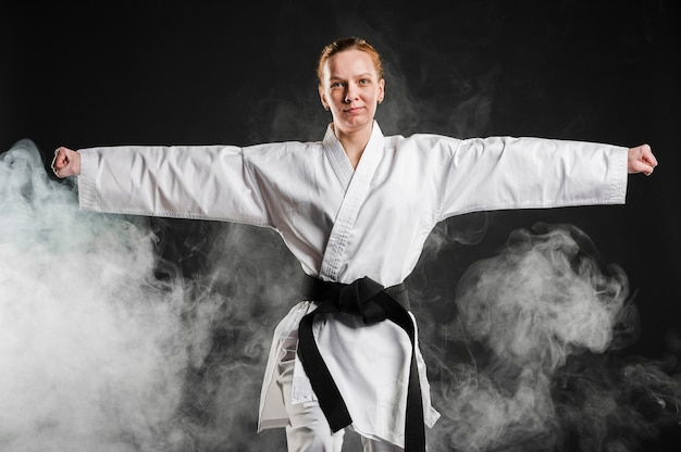Frau im kimono, der taekwondo übt