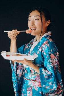 Frau im kimono isst sushi-rollen