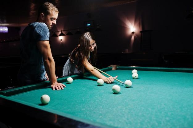 Frau im kleid, das pool mit einem mann in einer kneipe spielt.