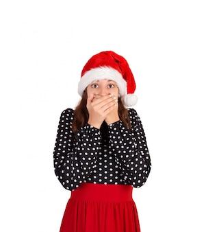 Frau im kleid erschrocken und schließt den mund mit den händen. emotionales mädchen im weihnachtsmann-weihnachtshut lokalisiert