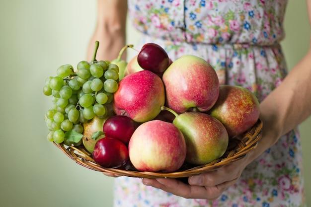 Frau im kleid hält einen korb mit reifen früchten