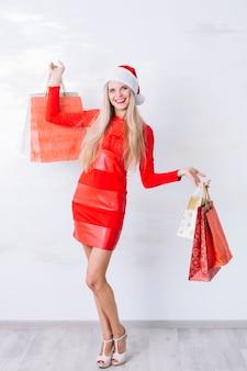 Frau im kleid mit einkaufstaschen in den händen