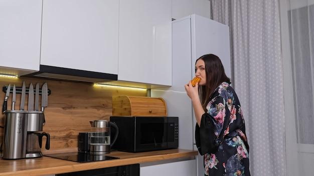 Frau im kleid schleicht sich an einen großen kühlschrank, um kuchen zu holen