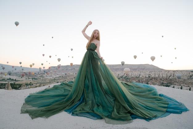 Frau im kleid unter ballonen in cappadocia