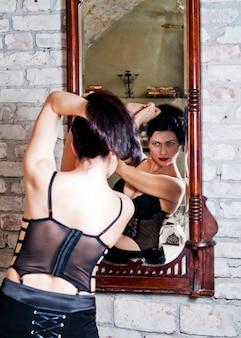 Frau im korsett vor einem spiegel
