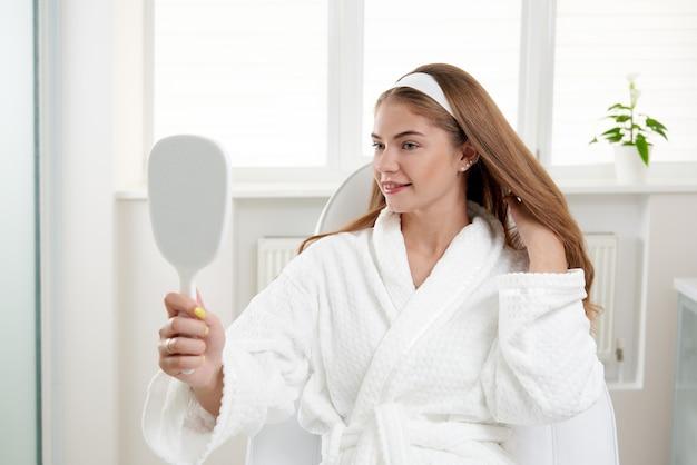 Frau im kosmetiksalon zufrieden mit dem ergebnis des kosmetischen verfahrens weiblich mit blick auf den spiegel und