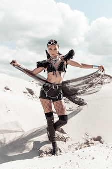 Frau im kreativen festival-outfit, das in der wüste aufwirft