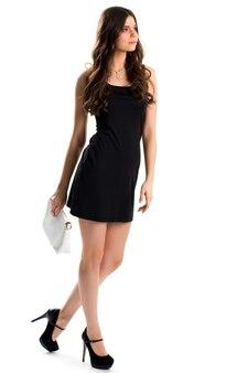 Frau im kurzen schwarzen kleid. dunkle schuhe auf high heels. designerkleidung und teurer schmuck. junges und hübsches modell.