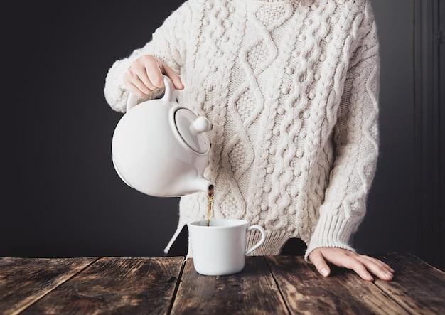 Frau im kuscheligen warmen weißen dicken strickpullover gießt heißen tee von der großen keramik-teekanne zur leeren tasse