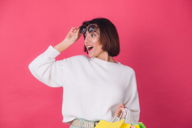 Frau im lässigen weißen pullover und in der sonnenbrille an der roten wand