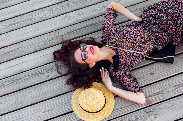 Frau im langen bunten kleid und im strohhut, die auf dem holzboden liegend liegen