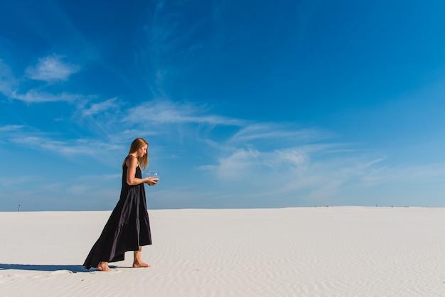 Frau im langen schwarzen kleid mit aquarium in der wüste