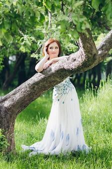 Frau im langen weißen kleid im sommergarten