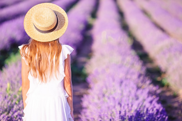 Frau im lavendelblumenfeld im weißen kleid und im hut