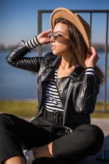 Frau im lederjacken-sitz auf dem pier nahe dem see im kalten sonnigen herbsttag