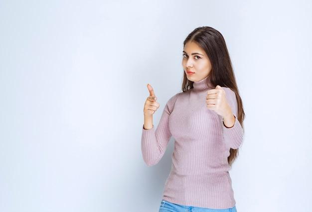 Frau im lila hemd, das ihre mächtigen fäuste zeigt.
