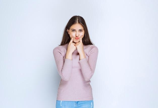 Frau im lila hemd, die auf ihr lächeln zeigt.