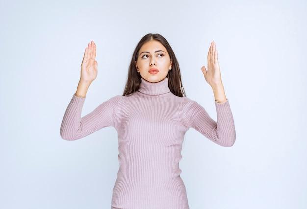 Frau im lila hemd, die die größe von etwas zeigt.