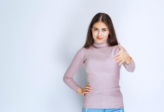 Frau im lila hemd, die hand gibt, um jemanden zu begrüßen.