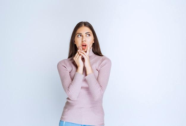 Frau im lila hemd, die ihre zunge herausstreckt.